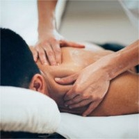 physiotherapist massaging neck and back of dark haired man